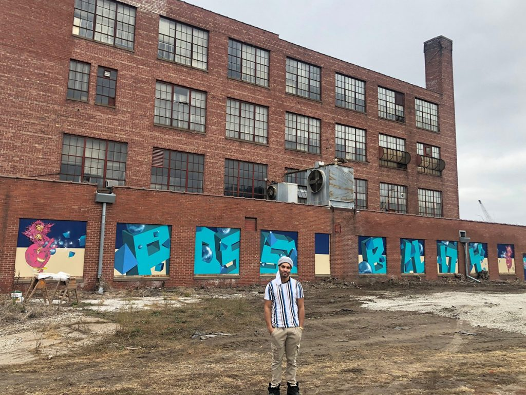 Artist Brandon Nees poses with his mural at the Spiegel Building